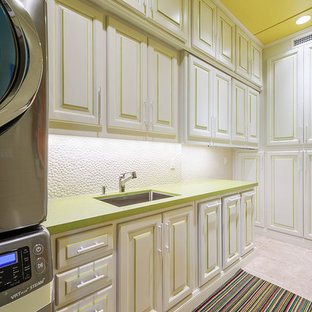 Inspiration for a tropical beige floor dedicated laundry room remodel in Los Angeles with an undermount sink, raised-panel cabinets, white cabinets and green countertops