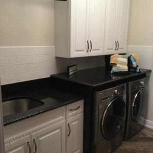 Inspiration för en mellanstor vintage linjär tvättstuga enbart för tvätt, med en enkel diskho, luckor med upphöjd panel, vita skåp, bänkskiva i kvarts, beige väggar, mellanmörkt trägolv och en tvättmaskin och torktumlare bredvid varandra