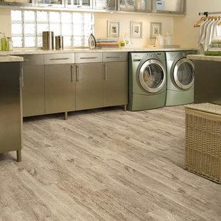 Foto på en stor vintage beige l-formad tvättstuga enbart för tvätt, med luckor med glaspanel, grå skåp, beige väggar, klinkergolv i porslin, en tvättmaskin och torktumlare bredvid varandra och grått golv