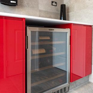 Exemple d'une buanderie linéaire moderne dédiée et de taille moyenne avec un évier posé, un placard avec porte à panneau encastré, des portes de placard rouges, un mur gris, un sol en carrelage de céramique, un sol gris et un plan de travail blanc.