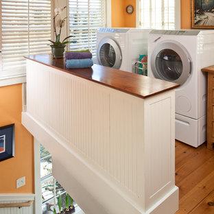 Exempel på ett litet klassiskt parallellt grovkök, med vita skåp, träbänkskiva, orange väggar och en tvättmaskin och torktumlare bredvid varandra