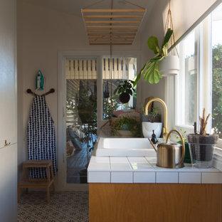 Esempio di una lavanderia multiuso classica di medie dimensioni con lavello stile country, ante in stile shaker, ante in legno chiaro, top piastrellato, pareti bianche, pavimento con piastrelle in ceramica, lavatrice e asciugatrice affiancate, pavimento multicolore e top bianco