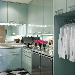 Foto di una lavanderia design con ante lisce, ante blu, lavatrice e asciugatrice affiancate e top in acciaio inossidabile