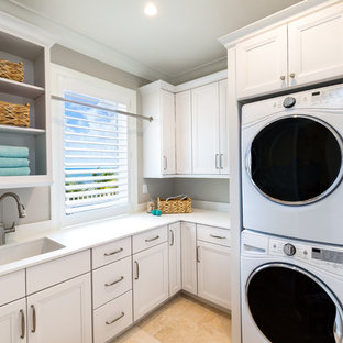 Dedicated laundry room - beach style l-shaped beige floor dedicated laundry room idea in Miami with an undermount sink, recessed-panel cabinets, white cabinets, gray walls, a stacked washer/dryer and white countertops