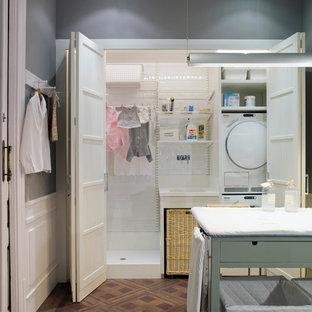 Ispirazione per una sala lavanderia mediterranea di medie dimensioni con ante in stile shaker, ante bianche, pareti grigie, pavimento in legno massello medio e lavatrice e asciugatrice a colonna
