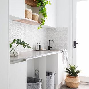 Foto di una sala lavanderia contemporanea di medie dimensioni con top in quarzo composito, pareti bianche, pavimento in gres porcellanato, lavatrice e asciugatrice a colonna, pavimento grigio, top grigio, lavello da incasso, ante lisce e ante bianche
