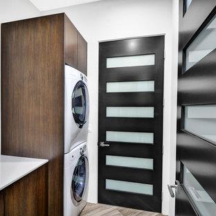 Idéer för mellanstora funkis linjära tvättstugor enbart för tvätt, med släta luckor, skåp i mellenmörkt trä, bänkskiva i glas, vita väggar, klinkergolv i porslin och en tvättpelare