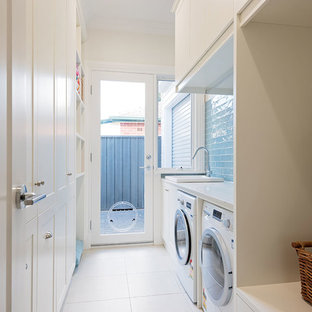 Dedicated laundry room - mid-sized transitional galley ceramic tile and white floor dedicated laundry room idea in Adelaide with a drop-in sink, shaker cabinets, white cabinets, granite countertops, white walls, a side-by-side washer/dryer and white countertops