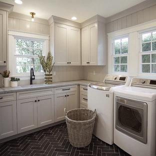 Idéer för en mellanstor klassisk grå l-formad tvättstuga enbart för tvätt, med en undermonterad diskho, skåp i shakerstil, grå skåp, bänkskiva i kvarts, grått stänkskydd, stänkskydd i trä, vita väggar, kalkstensgolv, en tvättmaskin och torktumlare bredvid varandra och svart golv