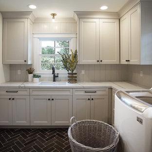 Inspiration för en mellanstor vintage grå l-formad grått tvättstuga enbart för tvätt, med en undermonterad diskho, skåp i shakerstil, grå skåp, bänkskiva i kvarts, grått stänkskydd, stänkskydd i trä, vita väggar, kalkstensgolv, en tvättmaskin och torktumlare bredvid varandra och svart golv