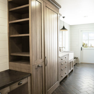 Inspiration for a mid-sized transitional single-wall dedicated laundry room in Phoenix with a farmhouse sink, shaker cabinets, medium wood cabinets, wood benchtops, grey splashback, timber splashback, white walls, limestone floors, a concealed washer and dryer, black floor, black benchtop and wood walls.