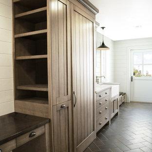 Inspiration för mellanstora klassiska linjära svart tvättstugor enbart för tvätt, med en rustik diskho, skåp i shakerstil, skåp i mellenmörkt trä, träbänkskiva, grått stänkskydd, stänkskydd i trä, vita väggar, kalkstensgolv, tvättmaskin och torktumlare byggt in i ett skåp och svart golv