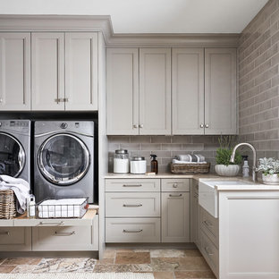 Design ideas for a large transitional l-shaped laundry room in Other with a farmhouse sink, recessed-panel cabinets, grey cabinets, white splashback, stone slab splashback, travertine floors, marble benchtops, a side-by-side washer and dryer, beige floor and beige benchtop.