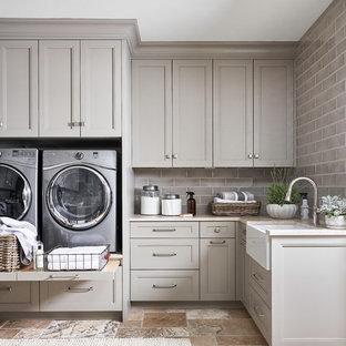 Inredning av en klassisk stor beige l-formad beige tvättstuga, med en rustik diskho, luckor med infälld panel, grå skåp, vitt stänkskydd, stänkskydd i sten, travertin golv, marmorbänkskiva, en tvättmaskin och torktumlare bredvid varandra och beiget golv