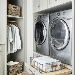 Klassisk inredning av en stor vita l-formad vitt tvättstuga, med en rustik diskho, luckor med infälld panel, grå skåp, vitt stänkskydd, stänkskydd i sten, travertin golv, flerfärgat golv, marmorbänkskiva, vita väggar och en tvättmaskin och torktumlare bredvid varandra