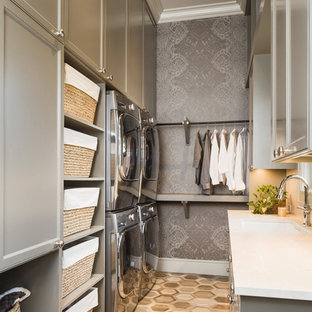 Dedicated laundry room - mid-sized transitional galley porcelain tile and brown floor dedicated laundry room idea in Austin with an undermount sink, recessed-panel cabinets, gray cabinets, marble countertops, gray walls, a stacked washer/dryer and white countertops