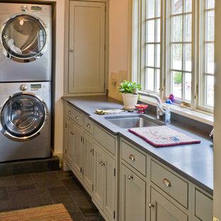 Klassisk inredning av en mellanstor l-formad tvättstuga, med luckor med profilerade fronter, grå skåp, bänkskiva i täljsten, beige väggar, skiffergolv, en tvättpelare och en undermonterad diskho