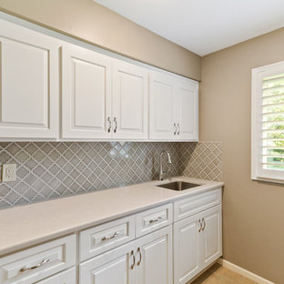 Photo of a mid-sized transitional single-wall dedicated laundry room in Kansas City with an undermount sink, raised-panel cabinets, white cabinets, quartz benchtops, beige walls, beige floor and turquoise benchtop.