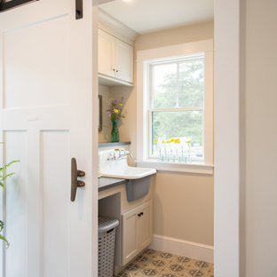 Inspiration for a beach style ceramic floor and multicolored floor dedicated laundry room remodel in Boston with a farmhouse sink, white cabinets, solid surface countertops, beige walls, gray countertops and recessed-panel cabinets