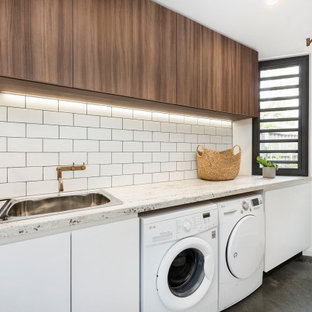 Photo of a mid-sized contemporary galley dedicated laundry room in Melbourne with a drop-in sink, flat-panel cabinets, medium wood cabinets, granite benchtops, white walls, concrete floors, a side-by-side washer and dryer, grey floor and white benchtop.