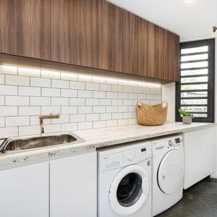 Inspiration för en mellanstor funkis vita parallell vitt tvättstuga enbart för tvätt, med en nedsänkt diskho, släta luckor, skåp i mellenmörkt trä, granitbänkskiva, vita väggar, betonggolv, en tvättmaskin och torktumlare bredvid varandra och grått golv
