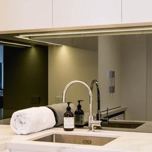 Inspiration för en liten vintage flerfärgade l-formad flerfärgat tvättstuga enbart för tvätt, med en undermonterad diskho, släta luckor, vita skåp, bänkskiva i kvarts, vita väggar, ljust trägolv, en tvättmaskin och torktumlare bredvid varandra och gult golv