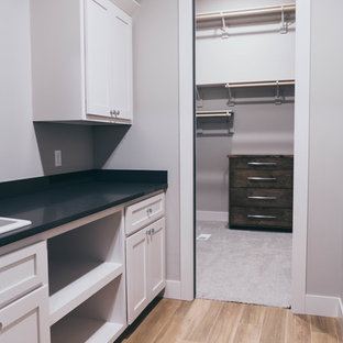 Modern galley separated utility room in Omaha with a built-in sink, shaker cabinets, white cabinets, engineered stone countertops, porcelain flooring, a side by side washer and dryer and black worktops.