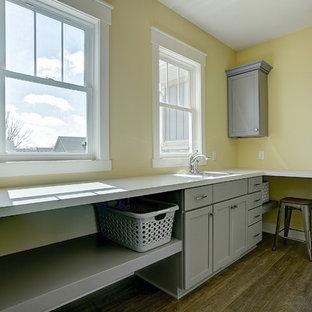 Bild på en liten amerikansk parallell tvättstuga enbart för tvätt, med en nedsänkt diskho, skåp i shakerstil, grå skåp, laminatbänkskiva, gula väggar, mellanmörkt trägolv, en tvättmaskin och torktumlare bredvid varandra och brunt golv