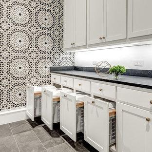 ダラスのコンテンポラリースタイルのおしゃれな洗濯室 (ll型、アンダーカウンターシンク、シェーカースタイル扉のキャビネット、白いキャビネット、クオーツストーンカウンター、マルチカラーの壁、セラミックタイルの床、左右配置の洗濯機・乾燥機、グレーの床、青いキッチンカウンター) の写真