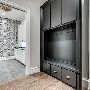 Inspiration för en funkis blå parallell blått tvättstuga enbart för tvätt, med en undermonterad diskho, skåp i shakerstil, vita skåp, bänkskiva i kvarts, flerfärgade väggar, klinkergolv i keramik, en tvättmaskin och torktumlare bredvid varandra och grått golv