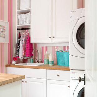 Idée de décoration pour une buanderie parallèle tradition dédiée avec un évier posé, un placard avec porte à panneau surélevé, des portes de placard blanches, un plan de travail en bois, un mur rose, des machines superposées et un sol rose.