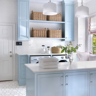 Dedicated laundry room - large traditional galley porcelain floor and gray floor dedicated laundry room idea in St Louis with blue cabinets, marble countertops, white walls, a side-by-side washer/dryer, white countertops and beaded inset cabinets
