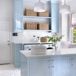 セントルイスの広いII型トラディショナルスタイルの洗濯室の画像 (青いキャビネット、大理石カウンター、白い壁、磁器タイルの床、左右配置の洗濯機・乾燥機、グレーの床、白いキッチンカウンター、インセット扉のキャビネット)