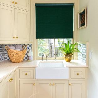 Idées déco pour une petit buanderie classique en L dédiée avec un évier de ferme, un placard à porte shaker, un sol en bois foncé, un plan de travail jaune, un plan de travail en quartz modifié, des portes de placard beiges et un mur blanc.