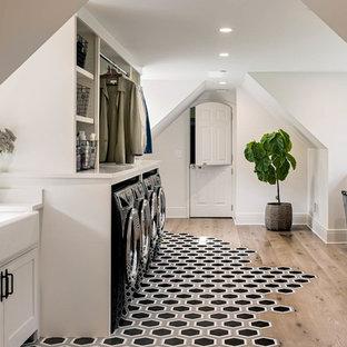 Lantlig inredning av en mellanstor parallell tvättstuga enbart för tvätt, med en rustik diskho, skåp i shakerstil, vita skåp, vita väggar, mellanmörkt trägolv, en tvättmaskin och torktumlare bredvid varandra och brunt golv