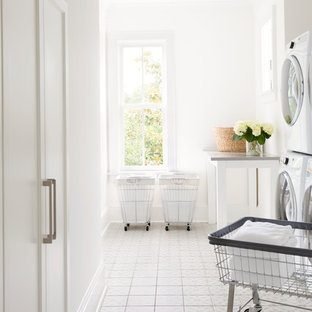 Dedicated laundry room - transitional galley ceramic floor and white floor dedicated laundry room idea in Charleston with white cabinets, white walls, a stacked washer/dryer, recessed-panel cabinets and gray countertops