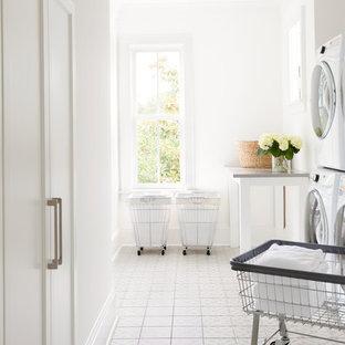 Immagine di una sala lavanderia tradizionale con ante bianche, pareti bianche, pavimento con piastrelle in ceramica, lavatrice e asciugatrice a colonna, pavimento bianco, ante con riquadro incassato e top grigio