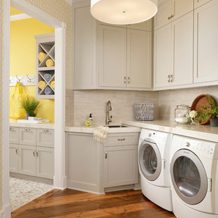 Dedicated laundry room - small transitional medium tone wood floor dedicated laundry room idea in Houston with an utility sink, shaker cabinets, gray cabinets, a side-by-side washer/dryer and yellow walls