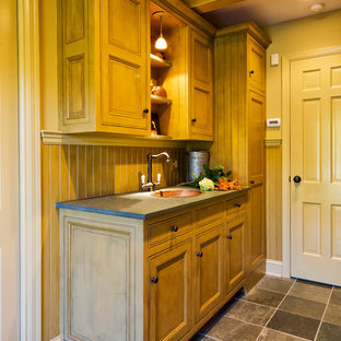 Example of a classic galley gray floor utility room design in New York with a drop-in sink, gray countertops, beaded inset cabinets, distressed cabinets, soapstone countertops, beige walls and a side-by-side washer/dryer