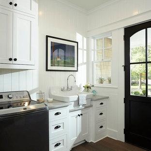 Immagine di una sala lavanderia tradizionale di medie dimensioni con lavello stile country, ante in stile shaker, ante bianche, top in granito, pareti bianche, parquet scuro, lavatrice e asciugatrice affiancate e pavimento marrone