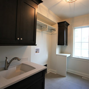 Large traditional single-wall separated utility room in Chicago with a submerged sink, shaker cabinets, dark wood cabinets, engineered stone countertops, white walls, concrete flooring, a side by side washer and dryer, grey floors and white worktops.