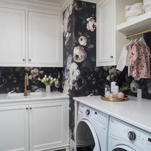 Immagine di una sala lavanderia tradizionale di medie dimensioni con lavello sottopiano, ante con riquadro incassato, ante bianche, pareti nere, lavatrice e asciugatrice affiancate, pavimento nero, top bianco, top in granito e pavimento con piastrelle in ceramica