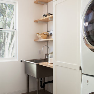 Example of a mid-sized country concrete floor and gray floor dedicated laundry room design in San Francisco with an utility sink, white cabinets, white walls, a stacked washer/dryer, shaker cabinets, wood countertops and beige countertops
