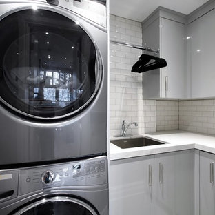 Photo of a mid-sized contemporary l-shaped dedicated laundry room in Toronto with an undermount sink, flat-panel cabinets, grey cabinets, laminate benchtops, grey walls, porcelain floors, a stacked washer and dryer and grey floor.