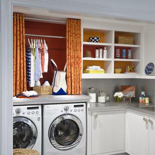 Immagine di una sala lavanderia tradizionale con ante bianche e top grigio