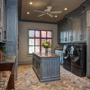 Foto di una grande sala lavanderia classica con lavello stile country, ante grigie, top in granito, pareti grigie, pavimento in mattoni, lavatrice e asciugatrice affiancate, pavimento beige e ante con riquadro incassato