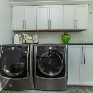 Inspiration for a large traditional galley utility room in Baltimore with shaker cabinets, white cabinets, composite countertops, grey walls, porcelain flooring, a side by side washer and dryer, grey floors and black worktops.