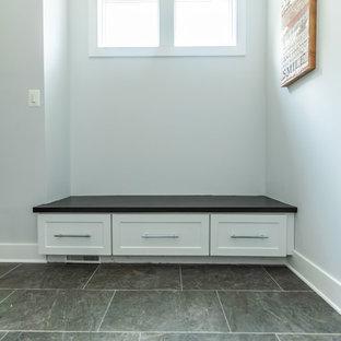 Foto di una grande lavanderia multiuso stile americano con ante in stile shaker, ante bianche, top in superficie solida, pareti grigie, pavimento in gres porcellanato, lavatrice e asciugatrice affiancate, pavimento grigio e top nero
