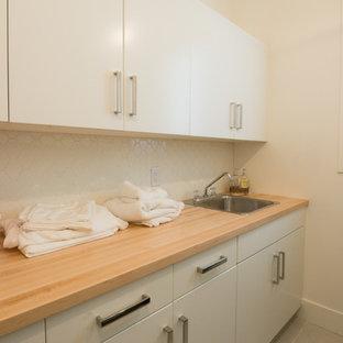 Foto på en liten funkis linjär tvättstuga, med en nedsänkt diskho, släta luckor, vita skåp, träbänkskiva och plywoodgolv
