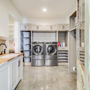 Foto di una lavanderia multiuso country con lavello sottopiano, ante in stile shaker, ante beige, top in legno, pareti bianche, pavimento in cemento, lavatrice e asciugatrice affiancate, pavimento grigio e top beige